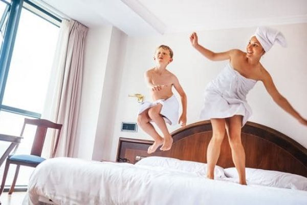 Mother and son jump on bed in luxury hotel room