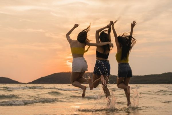 Group of three Asian young women jumping on beach, friends happy relax having fun playing on beach near sea when sunset in evening. Lifestyle friends travel holiday vacation on beach summer concept.