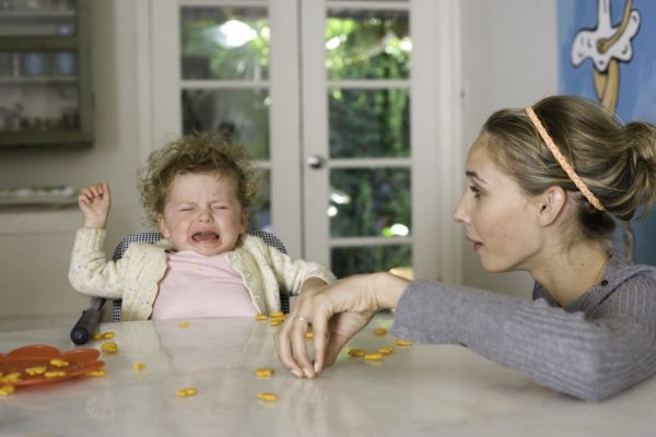 Toddler struggling and crying in high chair while woman picks up goldfish snacksat the dining table.