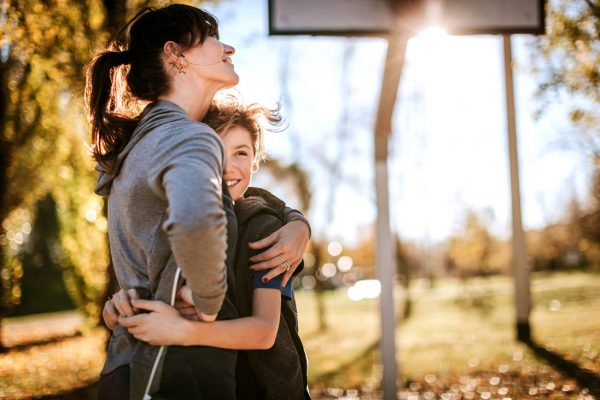 Beautiful mother hugging her son on basketball field on sunny autumn day